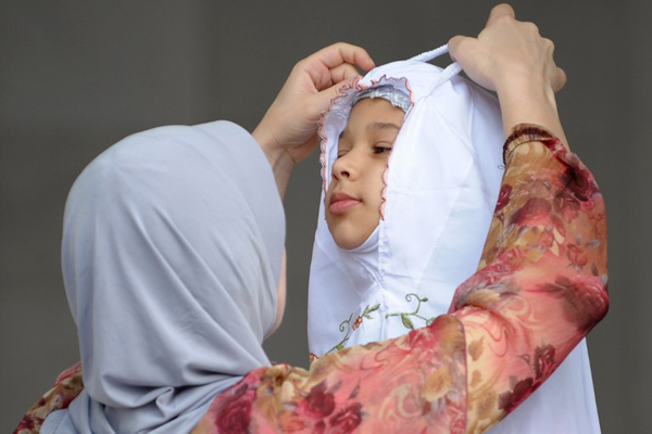 A mother adjusts her daughter's headscarf to celebrate the start of the three-day Eid al-Fitr festival in Kuala Lumpur on 30 August, 2011. Eid-al-Fitr celebrations mark the end of the fasting month of Ramadan. AFP PHOTO / Mohd Rasfan