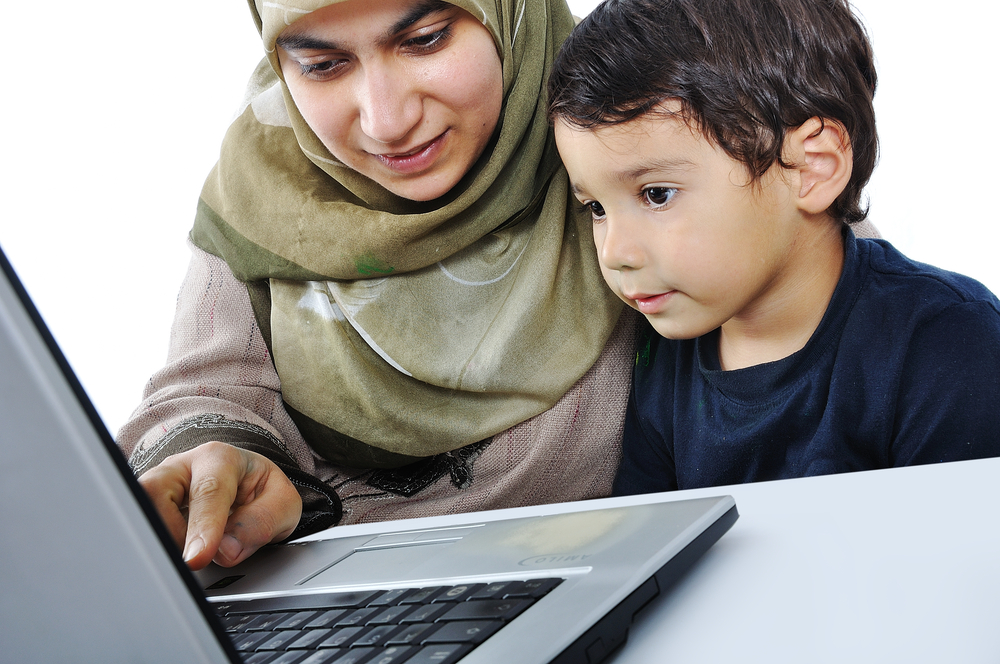 Muslim woman and her son on laptop